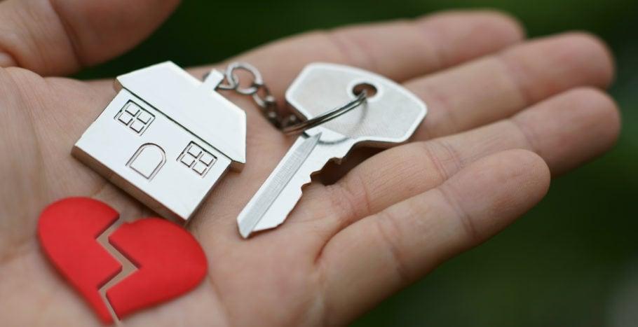 Avain kämmenellä, jossa talo avaimenperä ja särkynyt sydän