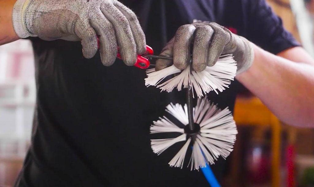 Putkimies valmistelee harjaa viemärihuoltoa varten